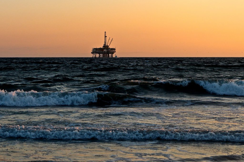 oil rig in ocean with a sunset