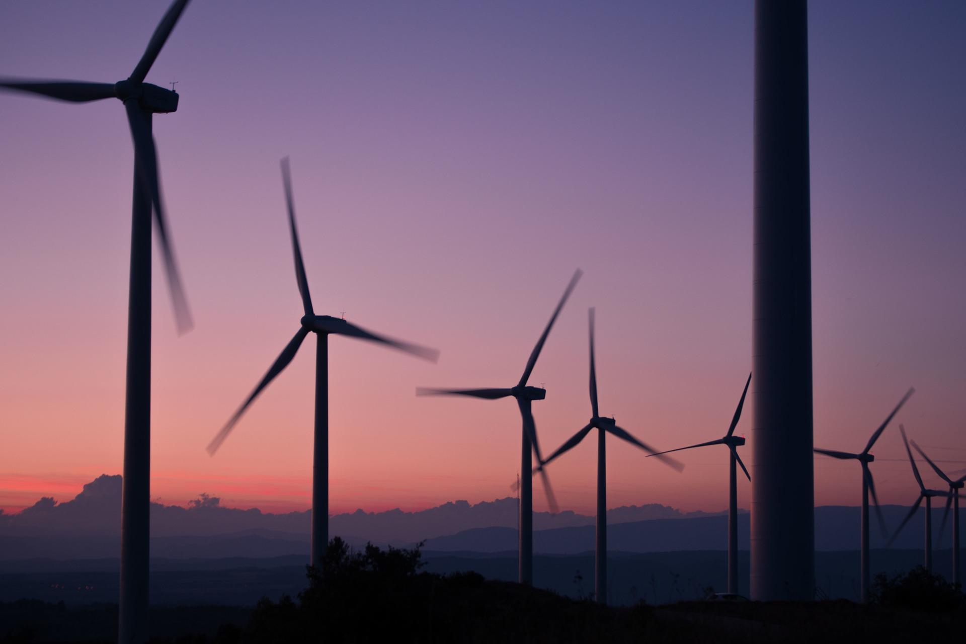 wind farm with a purple and orange sunset